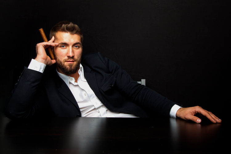 Attractive business man with a cigar One Person Beard Black Background Portrait Indoors  Facial Hair Looking At Camera Men Adult Dark Suit Businessman Mafia  Relaxing Casual Clothing Career Office Table Breakfast Handsome Attractive Bearded People Caucasian Smart