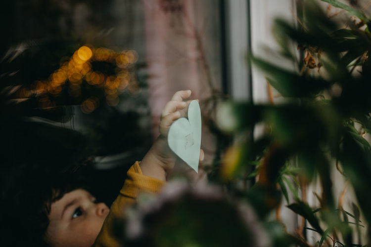 Girl sticking heart shape paper on window