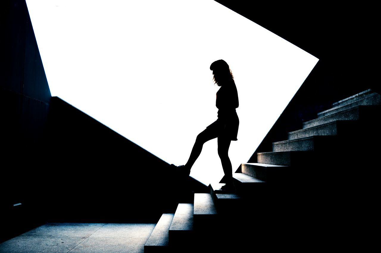 Side view of silhouette woman standing on steps