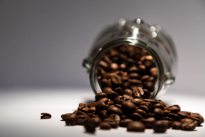 spilled coffee beans Brown Caffeine Close-up Coffee Coffee - Drink Coffee Bean Container Drink Food Food And Drink Freshness Indoors  Jar Large Group Of Objects No People Roasted Roasted Coffee Bean Selective Focus Still Life Table