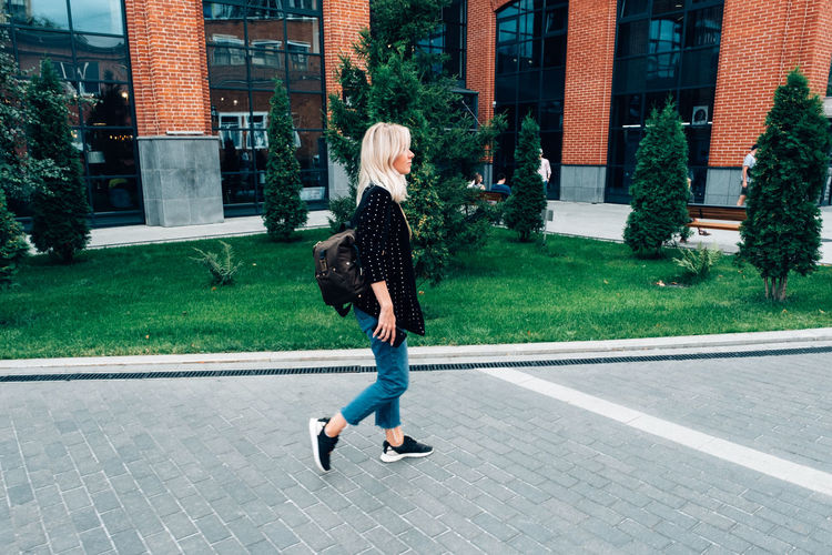 Full length rear view of woman walking on street in city