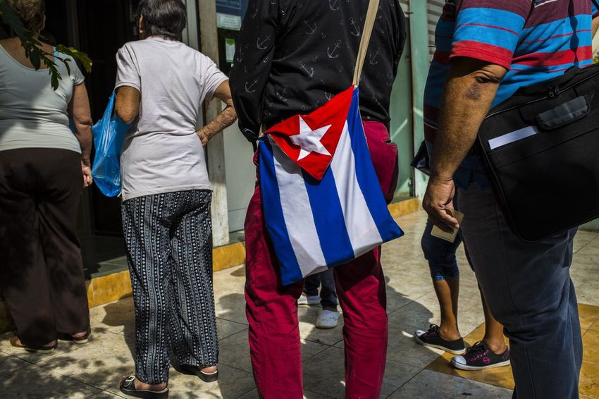 People queue to use an ATM outside a bank in Havana, Cuba. BestDestinatonSoFar Cuban Flag Queue Queueing Travel Adult Atm Bank Beauty Bestdestinations Day Flag Low Section Men Outdoors Patriotism People Real People Rear View Street Street Photography Streetphotography Togetherness Women