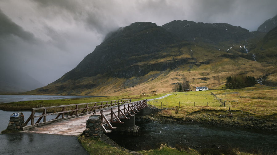 Beauty In Nature Bridge EyeEm Best Shots Cloud - Sky Crossing Path EyeEm Stormy Skies Lake Highlands IsolationLandscape Mountain Mountain Range Nature No People Outdoors River The Great Outdoors - 2017 EyeEm Awards Scotland Sky Stormy Weather Tranquility Tree Water