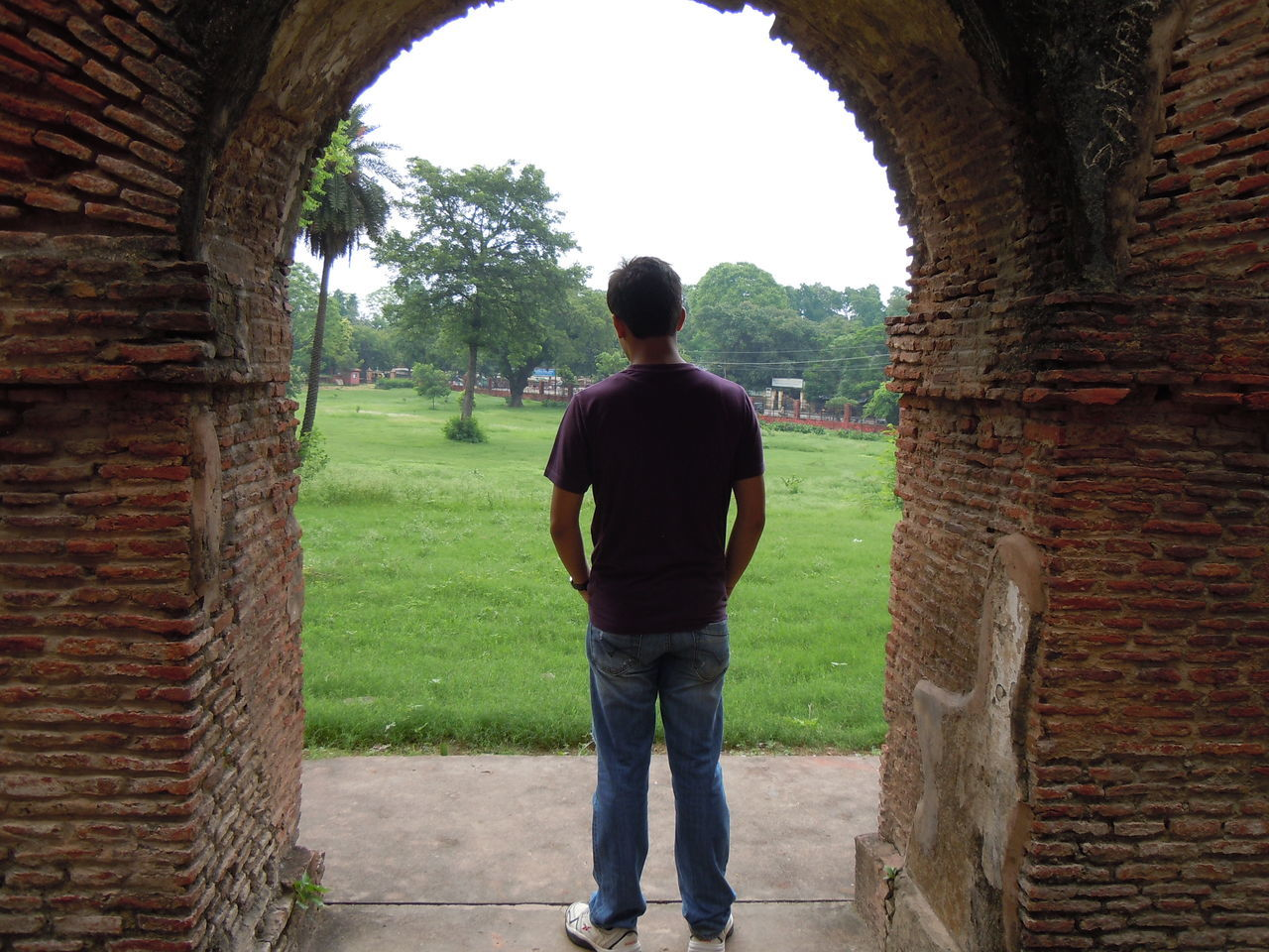 real people, rear view, brick wall, built structure, day, one person, arch, architecture, casual clothing, standing, full length, outdoors, lifestyles, leisure activity, men, tree, building exterior, nature, one man only, adult, people, adults only