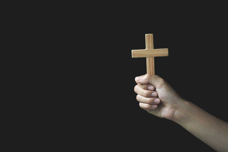 Close-up of hand holding cross against black background