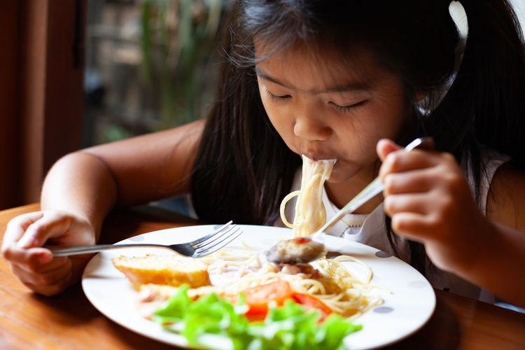 Girl eating noodles at home