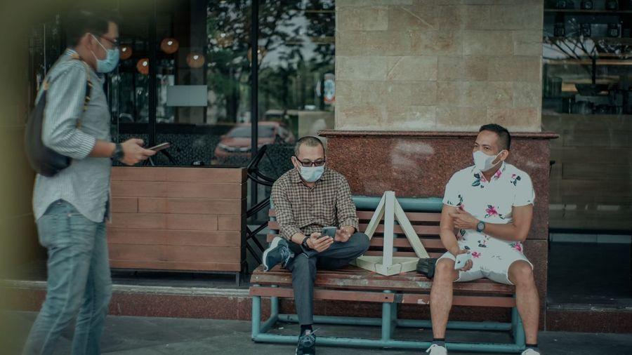 People sitting on table at sidewalk cafe