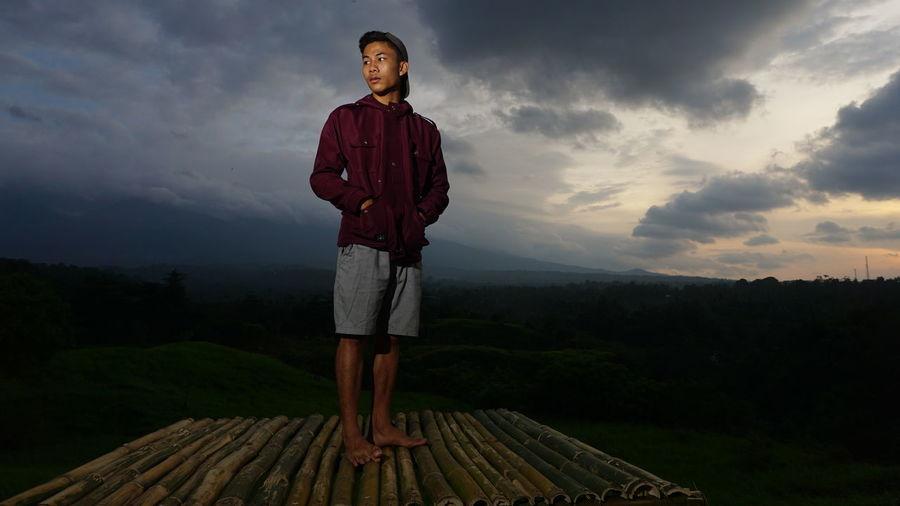 Man standing on wooden raft against sky
