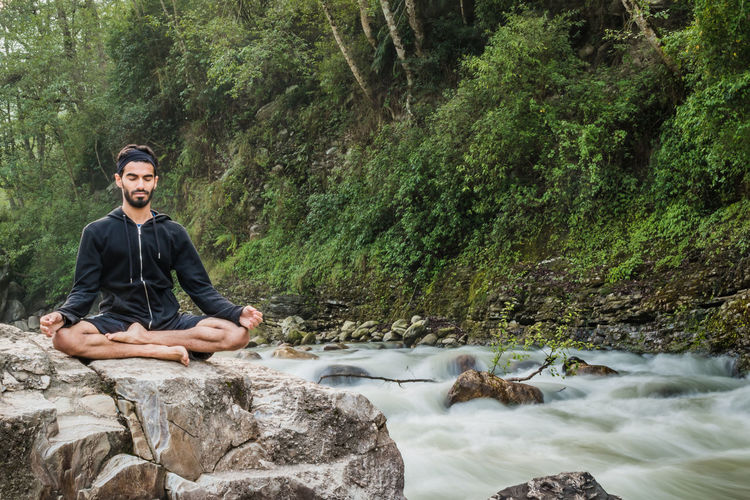 Full length of man practicing yoga on rock by stream