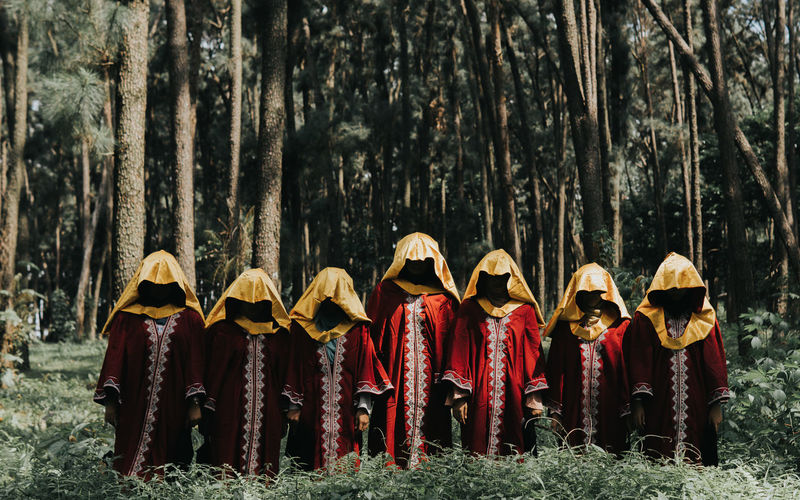 People wearing traditional clothing standing by trees