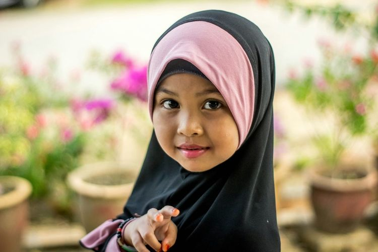 Portrait of cute girl in hijab outdoors