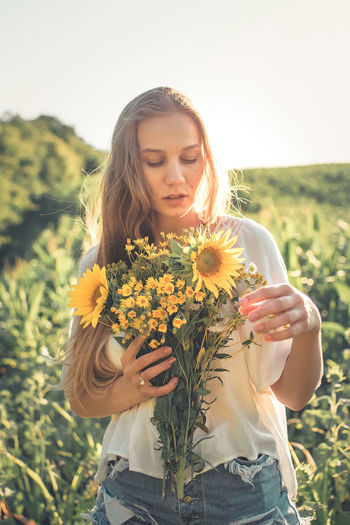 Beautiful young woman holding yellow flower in field
