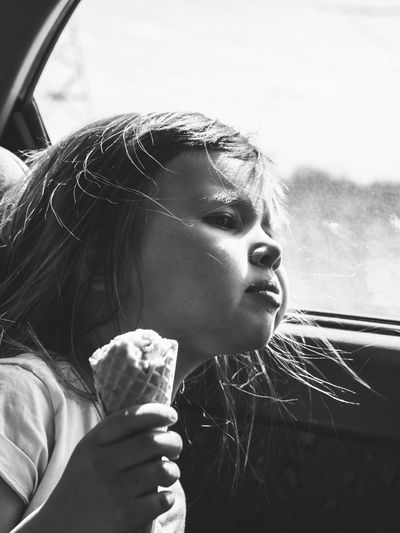 Girl Holding Ice Cream Cone While Looking Away In Car