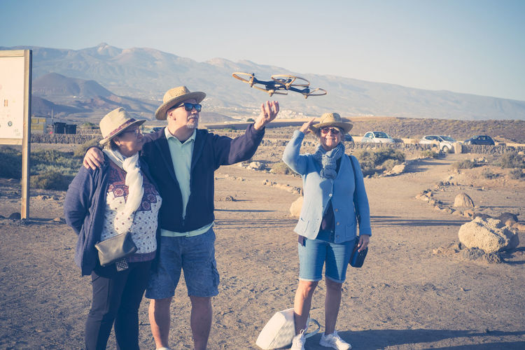 Friends flying drone while standing at desert