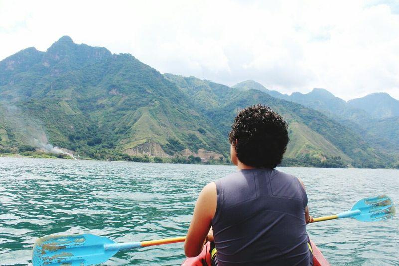 Rear view of man kayaking on lake by green mountains