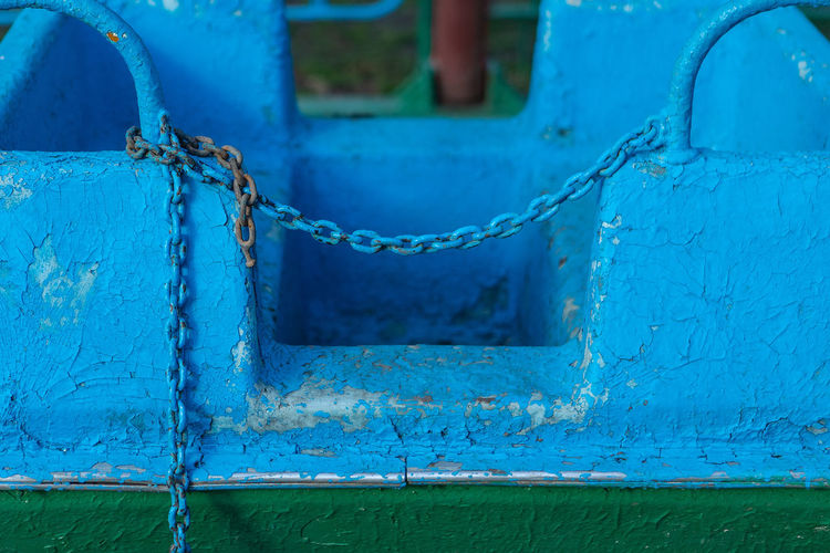 Close-up of rusty metal against blue wall