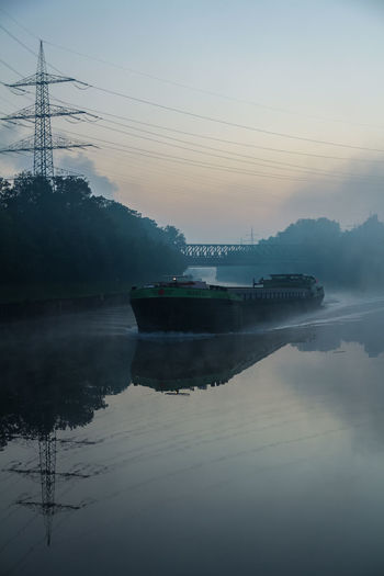 I was at the canal to shoot the sunrise... this happened 30min before. The first boat of the day came and I just had to take a picture with that clear reflection on the water. Boat Bottrop Business Finance And Industry Canal Day Deutschland Essen Germany Morning Nautical Vessel No People Outdoors Power Lines Reflection Rhein-Herne-Kanal  River Ruhrgebiet Ship Sky Tranquility Tree Water