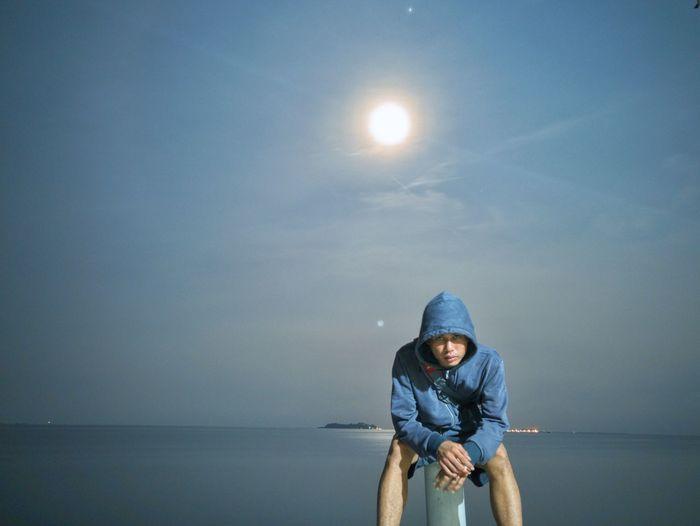 Portrait of man sitting on bollard by sea against sky