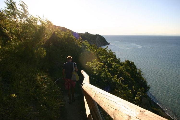 Man walking by railing at beach against clear sky