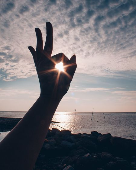 OKAY 2018 Human Hand Sea Human Body Part Sunset One Person Human Finger Real People Water Sun Horizon Over Water Personal Perspective Outdoors Sunlight Sky Beauty In Nature Nature Beach Silhouette Sunbeam Lifestyles EyeEm Ready