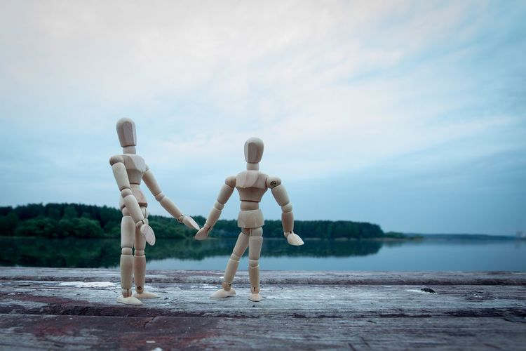 Wooden figurines on table against calm lake