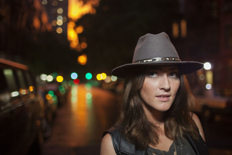 Portrait of woman wearing hat at night