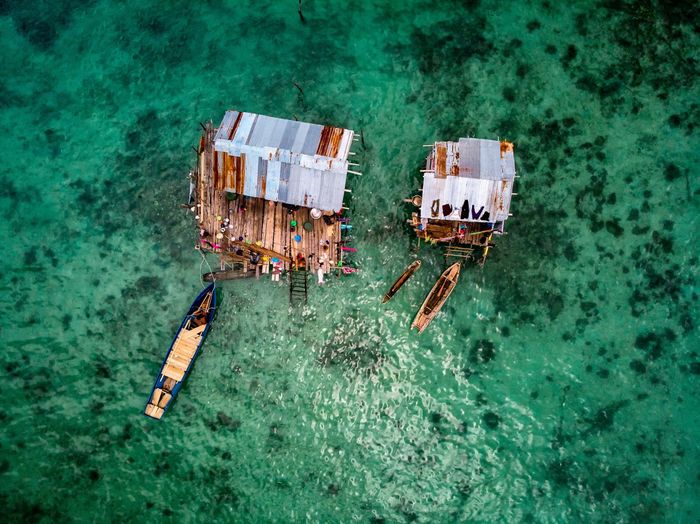 High angle view of stilt houses and boats on sea
