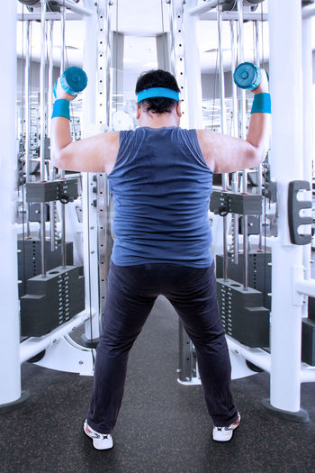 Full length of man holding dumbbell at gym
