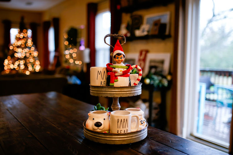 Elf on the Shelf Sitting In a Christmas Mug With Christmas Decorations Focus On Foreground Table Wood - Material Indoors  No People Christmas Christmas Decorations Christmas Decoration Christmas Lights Elf On The Shelf Elf Mug Coffee Maker Farmhouse Mama Papa Bear Mugs Coffee Mug Home Interior Home Decor Home Metal Industrial