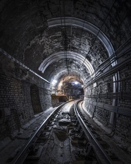 Illuminated railroad tracks in tunnel