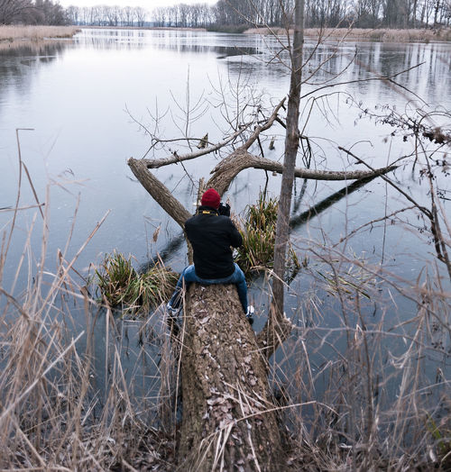 Man sitting on fallen tree against lake