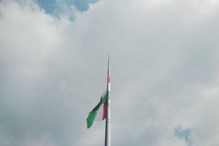 Low angle view of hungarian flag against cloudy sky