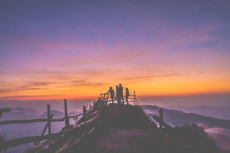 Silhouette Friends At Observation Point On Mountain Against Sky During Sunset