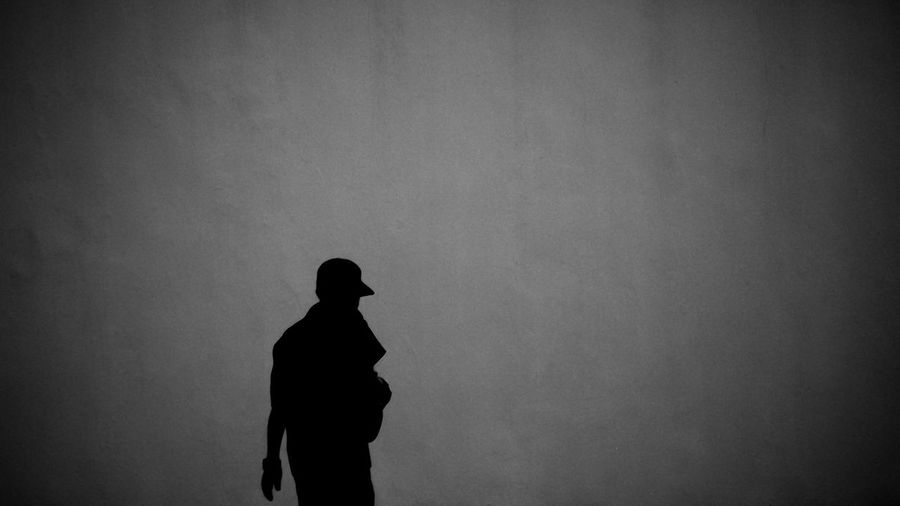 Silhouette man standing against wall