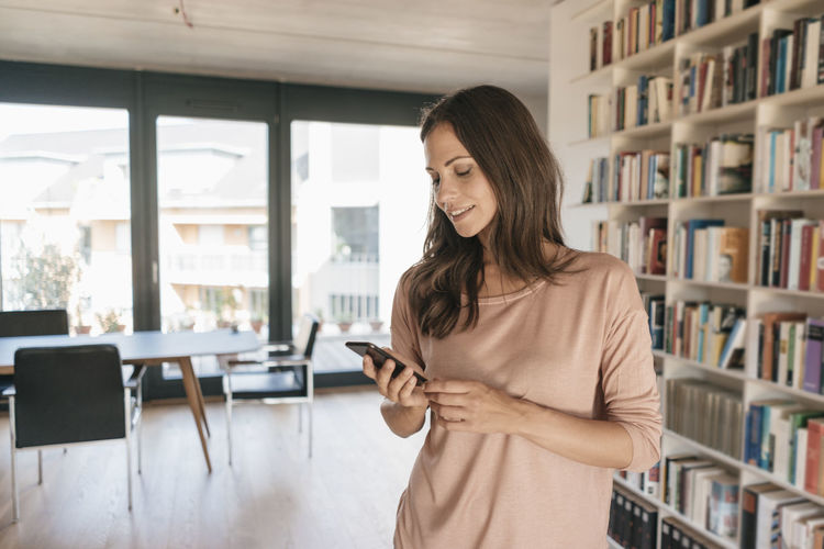 Woman using phone while standing on laptop