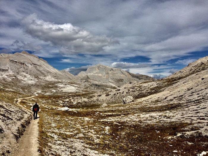 Man walking on mountain trail against sky