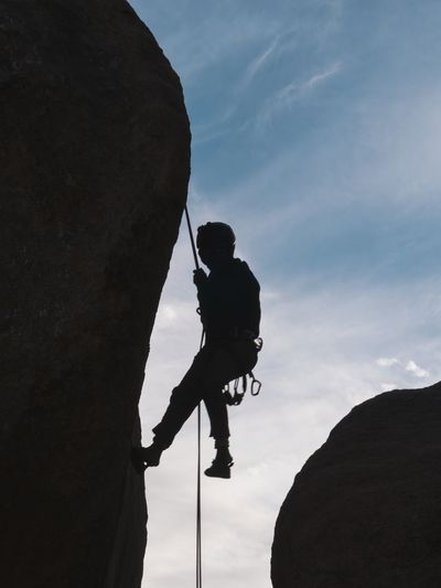 Low angle view of silhouette man climbing rock against sky