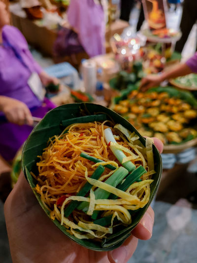 Close-up of hand holding thai noodle