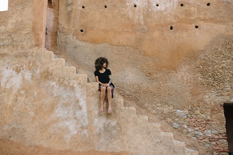 Woman sitting on staircase against building in city
