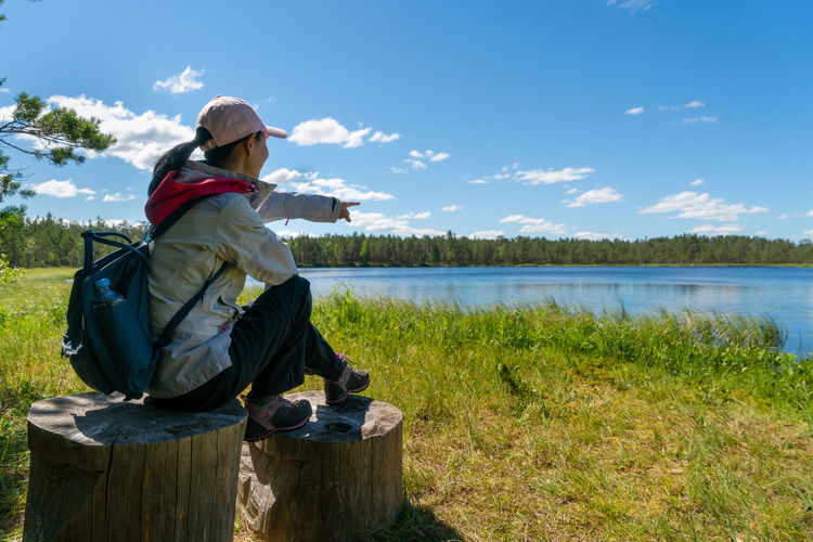 Side view of woman looking at lake against sky