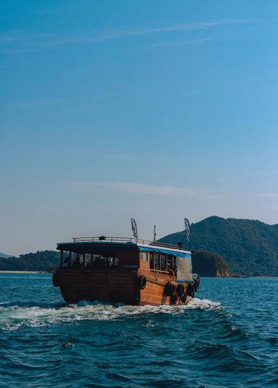 Ship sailing on sea against clear blue sky