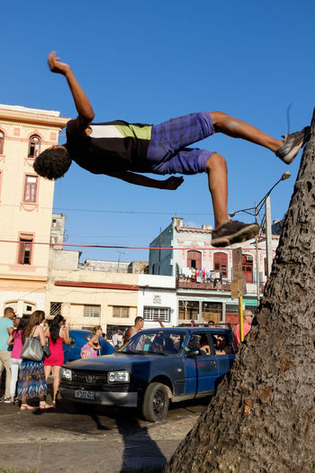 Young man performing stunt on tree trunk