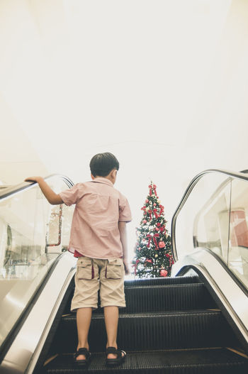 Young boy standing on escalator moving towards Christmas tree 5 Years Old Asian  Boy Casual Clothing Christmas Tree Copy Space Escalator Holiday Indoors  Kid Leisure Activity Lifestyles Moving Up Rear View Season  Standing The Culture Of The Holidays Traveling Home For The Holidays