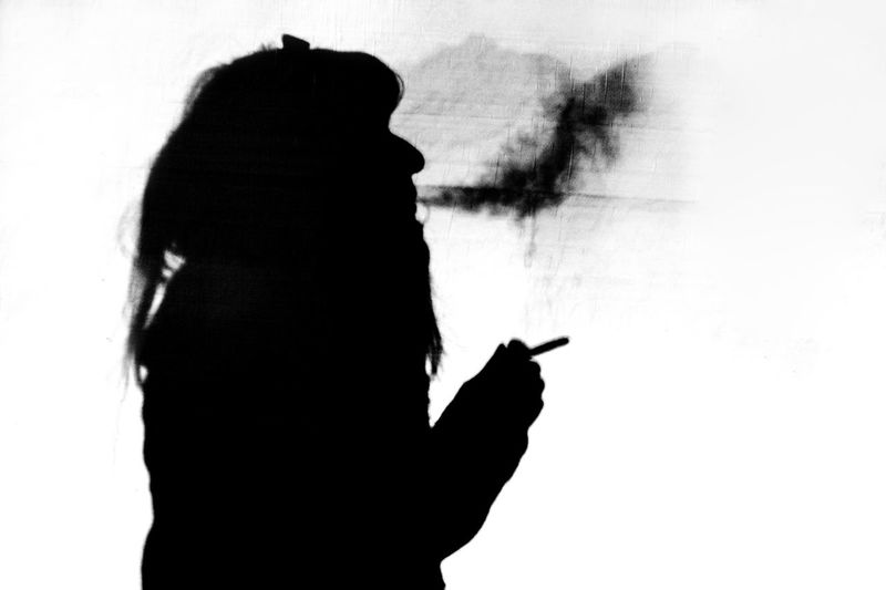 Silhouette woman hand against sky