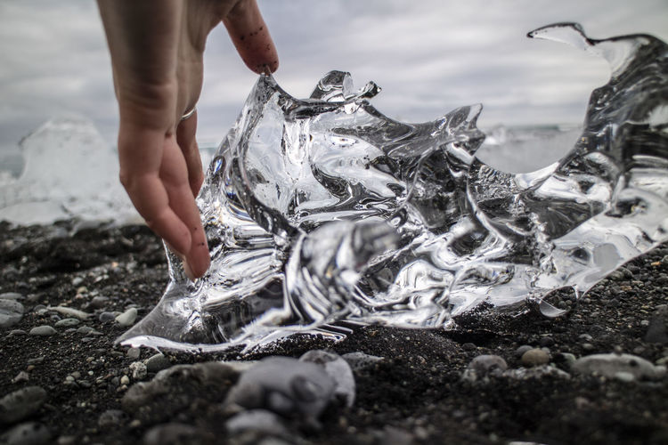 Cropped Hand Of Woman Touching Ice On Black Sand At Beach