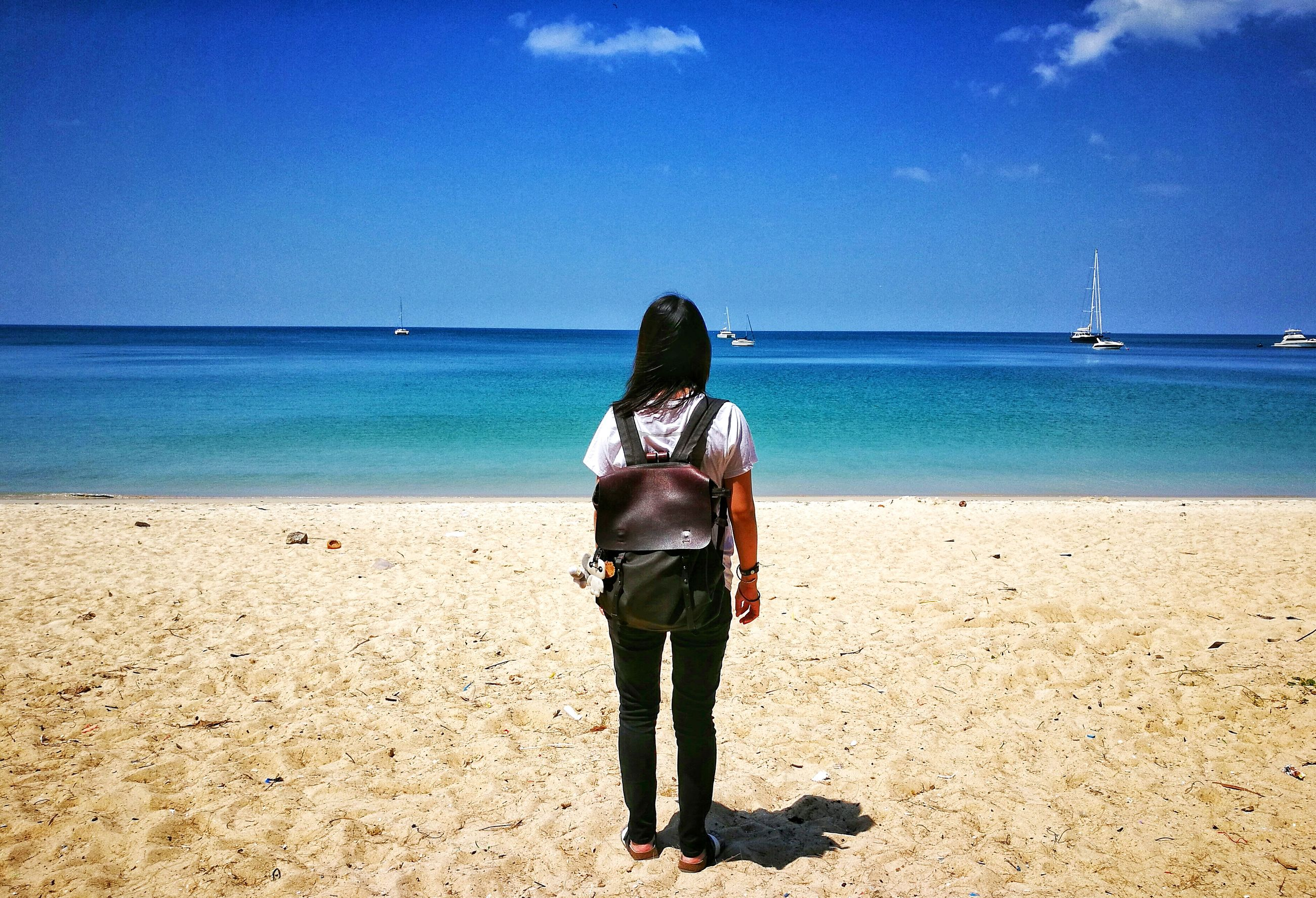 rear view, sea, horizon over water, beach, real people, water, sky, blue, one person, beauty in nature, leisure activity, sunlight, scenics, sand, outdoors, standing, nature, tranquility, day, men, adult, adults only, people