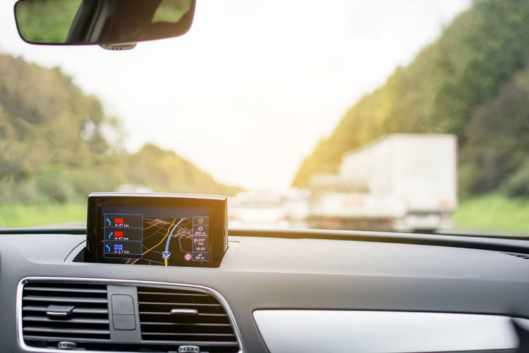 Satellite navigation system device in car with blurred transportation on highway road in Europe Satellite Navigation System Device Car Transportation Highway Road Mode Of Transportation Motor Vehicle Vehicle Interior Windshield Car Interior Travel City No People Technology Modern Display Vehicle