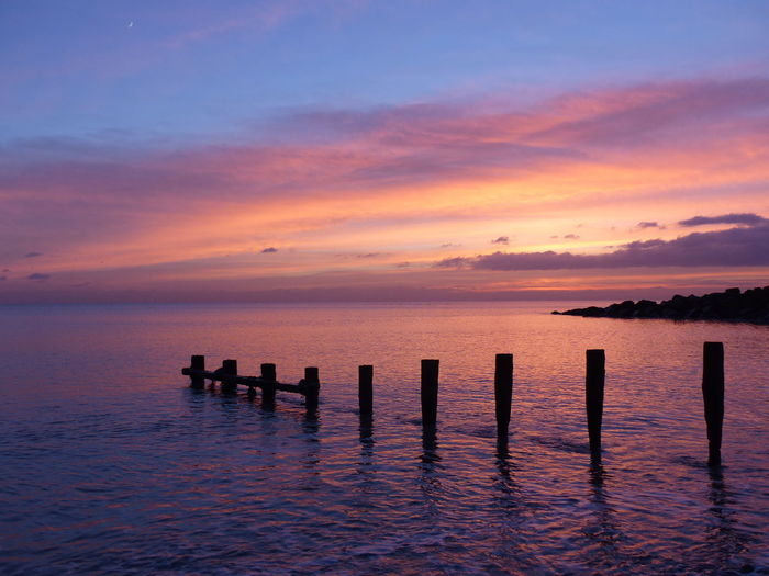 Silhouette wooden posts in sea against sky at sunset