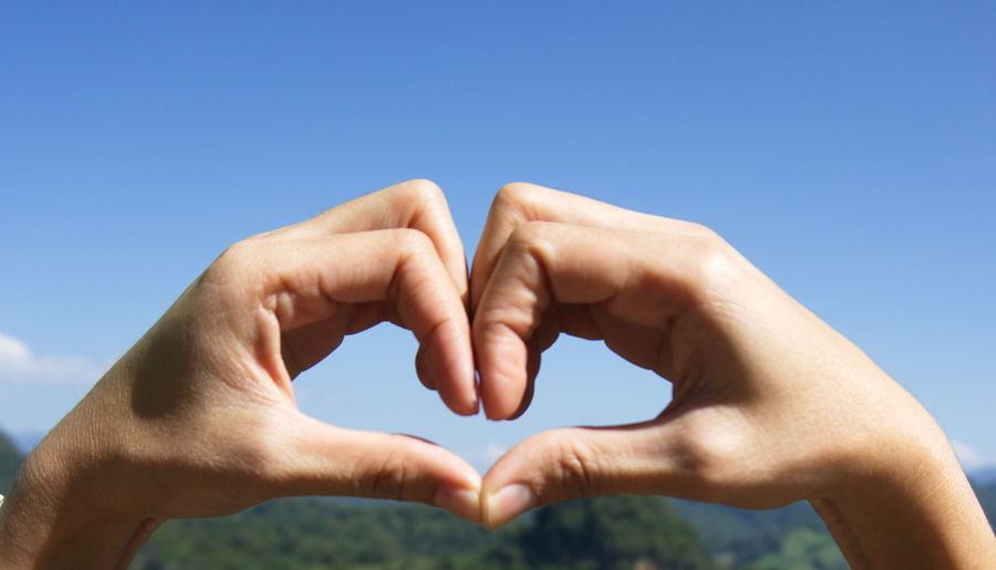 Cropped hands of person making heart shape against sky