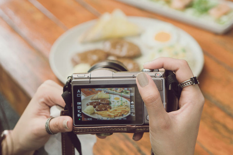 Midsection of man photographing with mobile phone on table